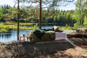 Kuva sängystä luonnon keskellä, nuku yö ulkona kampanjakuva